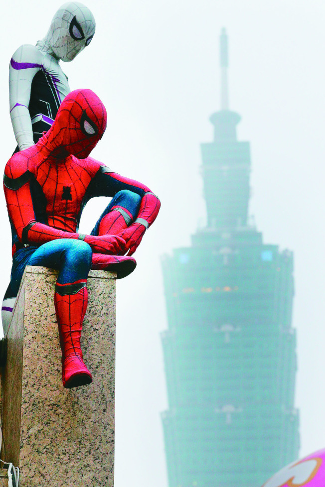 台北空汙嚴重,街頭藝人身著蜘蛛人裝扮,映襯著遠方的台北101大樓一片灰濛濛。(記者陳正興╱攝影)