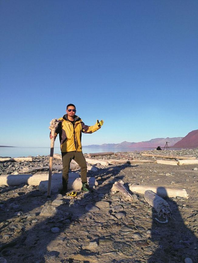 在北極斯瓦爾巴德群島登陸點,王榮撿到一根酷似權杖的木頭。(取材自華西都市報)