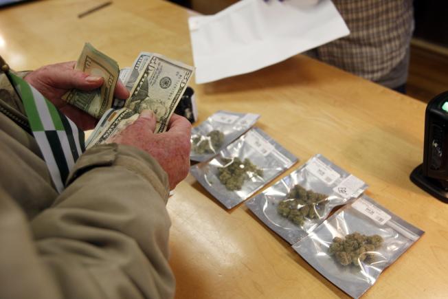 加州屋崙一家大麻經銷店1日湧入許多顧客上門,店員忙著交易。(美聯社)