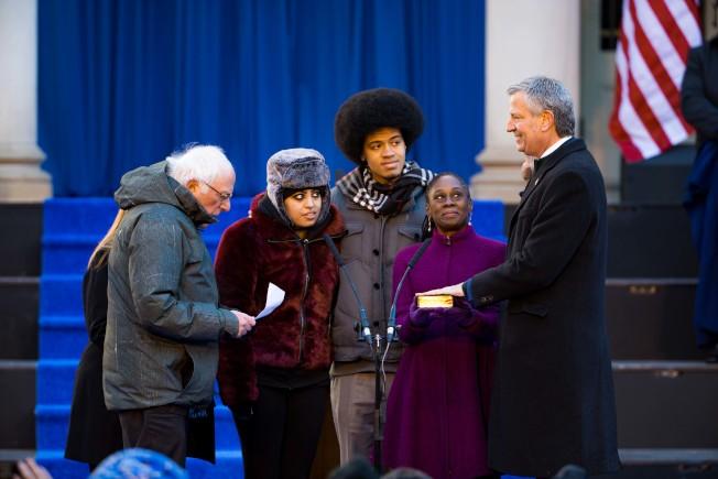 白思豪(右一)在妻子和一雙兒女環繞下,由桑德斯(左一)監誓就職第二任期。(市長辦公室提供)