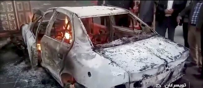 電視新聞截圖顯示,伊朗哈馬丹省有車輛被燒毀。(路透)