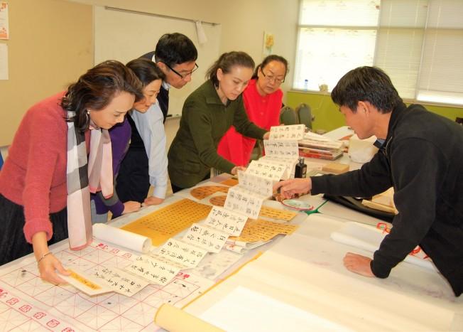 黃鑫老師(右)向書法愛好者們展示他的書法長卷。(記者賈忠/攝影)