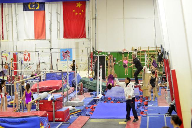 熊景斌協助隊員做後空翻動作,後方為美國教練進行訓練。(記者王政賢/攝影)