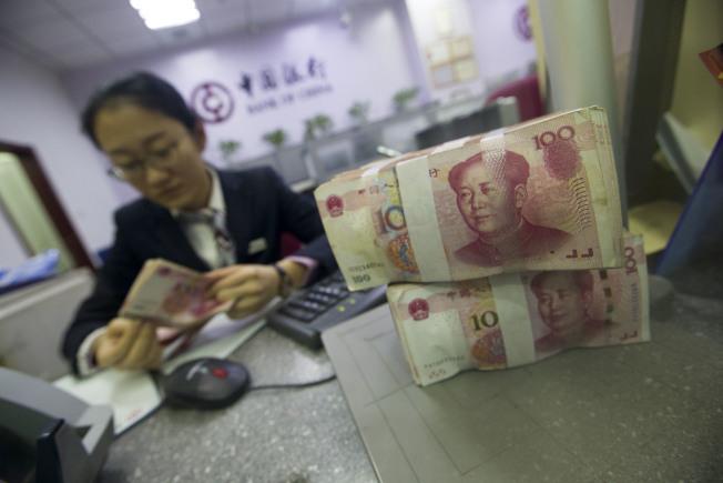 2018年首個交易日人民幣對美元匯率中間價創逾三個半月新高。圖為山西太原銀行工作人員2日正在清點貨幣。(中新社)