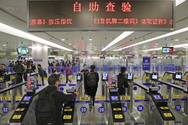 上海邊檢1日在浦東機場新增設21條出境自助通關通道。圖為旅客在浦東機場T2航站樓出境大廳內掃登機牌、刷護照、按指紋、拍照片。(中新社)