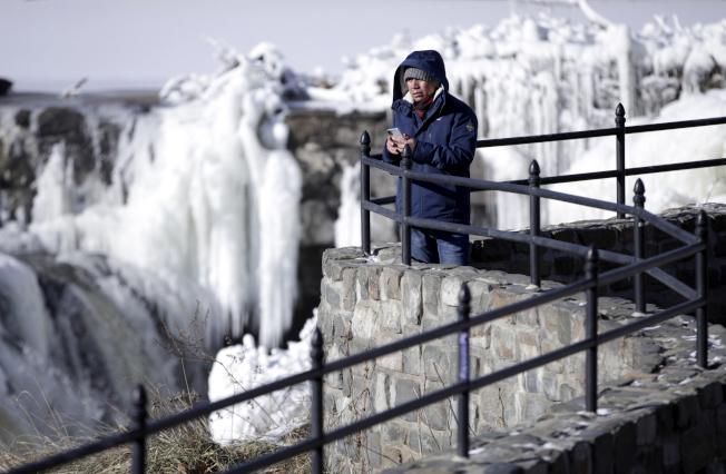 美北和美東酷寒,圖為新澤西州派特森一處瀑布被凍成「冰瀑」。(美聯社)
