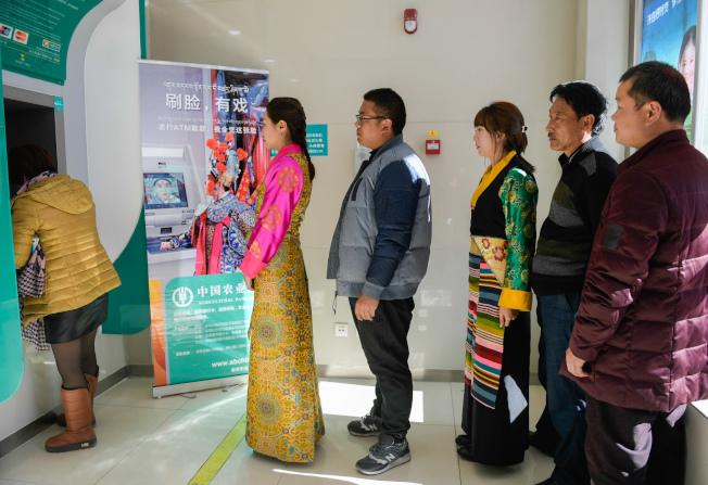 中國農業銀行西藏分行實現「刷臉取款」業務,圖為群眾在拉薩排隊等候取款。(新華社)