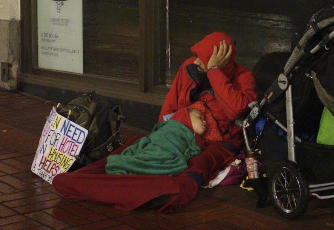 一名年輕父親帶著兒子在波特蘭市區高端旅館前面乞討。(美聯社)