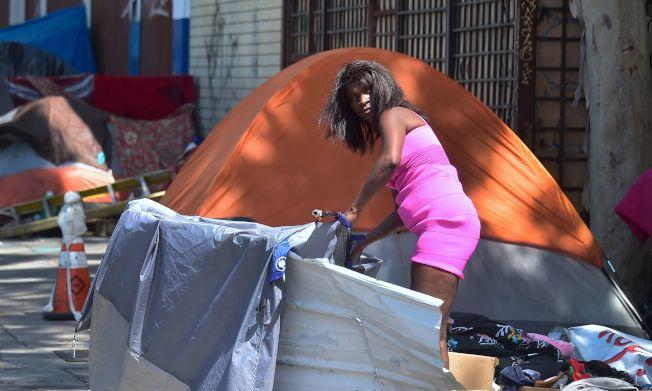 美國許多年輕人淪為街頭遊民,圖為一名年輕女性在洛杉磯街頭,利用路障搭起帳篷露宿。(Getty Images)
