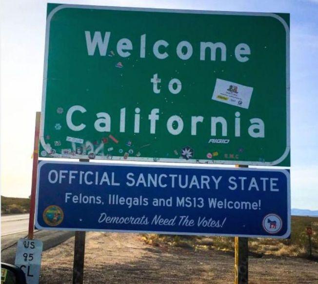 一個藍色標誌的文字是「歡迎到加州」,下方的說明是「加州是庇護州,罪犯、無證移民和MS13幫派分子都來者不拒,因為民主黨需要選票」。(取材自推特)