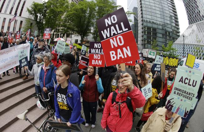 圖為去年5月,西雅圖示威者手舉標語牌,在聯邦法院外反對川普政府旅行禁令。(美聯社)
