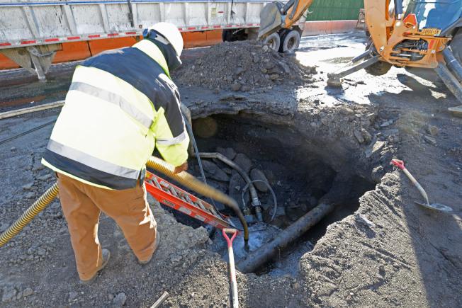 威利點出現十多呎深天坑,環保局人員搶修。(記者朱澤人/攝影)