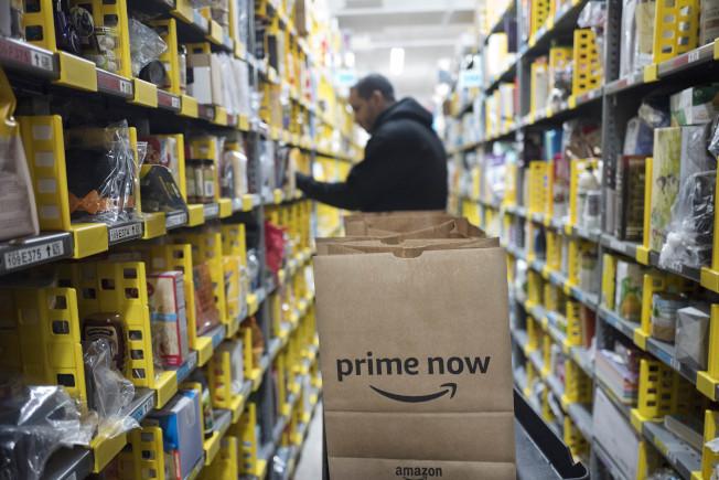 圖為紐約亞馬遜倉庫一名員工正在為消費者挑選訂購商品。(美聯社)