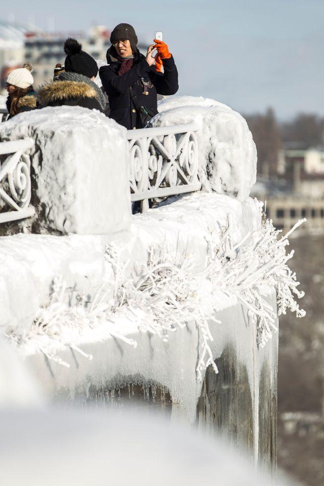 遊客在尼加拉瀑布拍照,急凍天氣已凍出許多冰枝。(美聯社)
