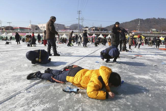 遊客6日在結冰的湖面洞口以垂釣或徒手抓的方式捕捉山川魚(鱒魚)。(美聯社)