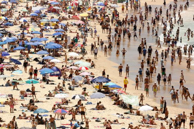 澳洲雪梨邦迪海灘擠滿消暑民眾。路透