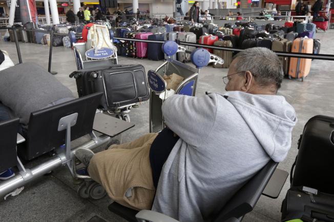 紐約市甘迺迪機場第四航站樓,一位旅客8日坐在抵達區域休息。(美聯社)
