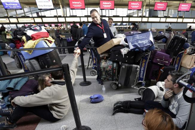 甘迺迪機場一名員工8日在第四航站樓為候機旅客發放三明治。(美聯社)