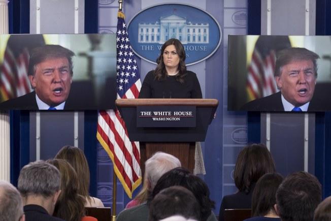 圖為白宮發言人桑德斯主持每日簡報時,旁邊的電視播出川普總統講話的畫面。(歐新社)
