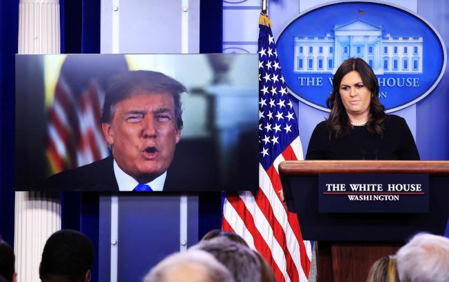圖為白宮發言人桑德斯主持每日簡報時,旁邊的電視播出川普總統講話的畫面。(美聯社)
