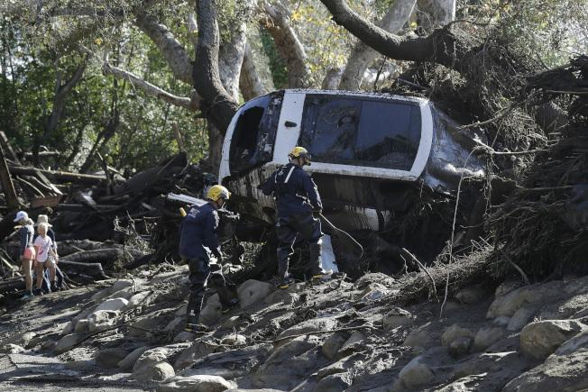 一輛汽車被土石流沖成側翻靠樹。(美聯社)
