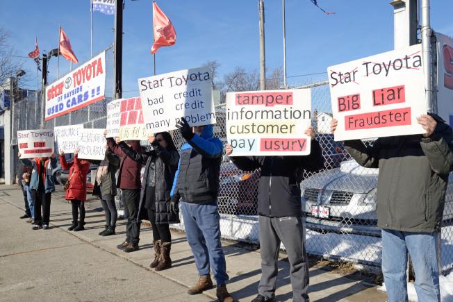 十多名華人10日舉牌抗議Star Toyota詐騙。(記者朱澤人/攝影)