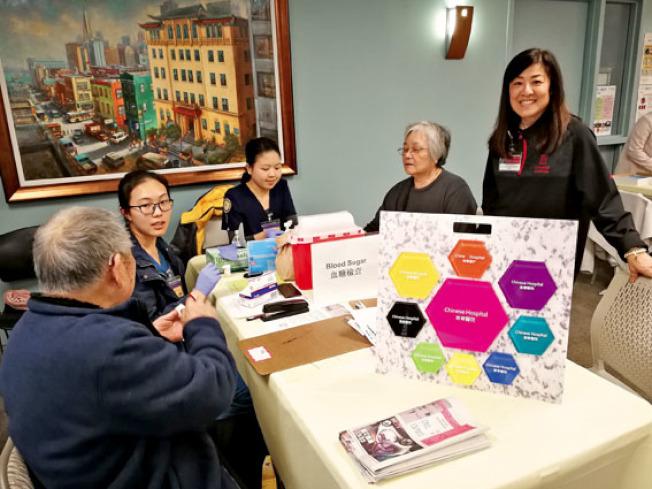 東華醫院的醫護人員為參加社區健康日的華埠居民檢查血糖及解答問題。(記者黃少華/攝影)