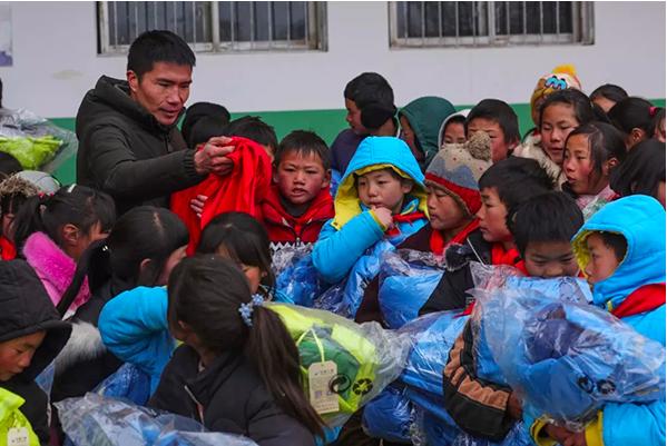 轉山包小學校長發放愛心衣物給學童。圖/擷取自「都市時報」微信公眾號
