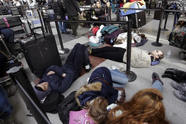 美東大風雪,被困甘迺迪機場的乘客橫七豎八的睡在地板上。(美聯社)