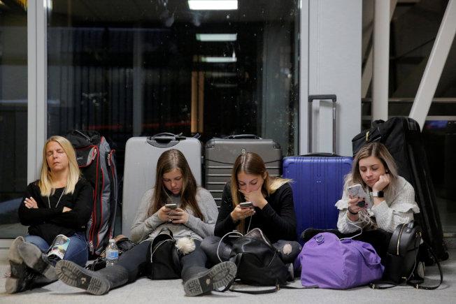 被困甘迺迪機場的四母女,用各種方法打發時間。(路透)