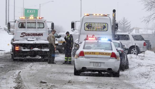 伊利諾州15日遭暴風雪侵襲後,警方在公路處理車禍事故。(美聯社)
