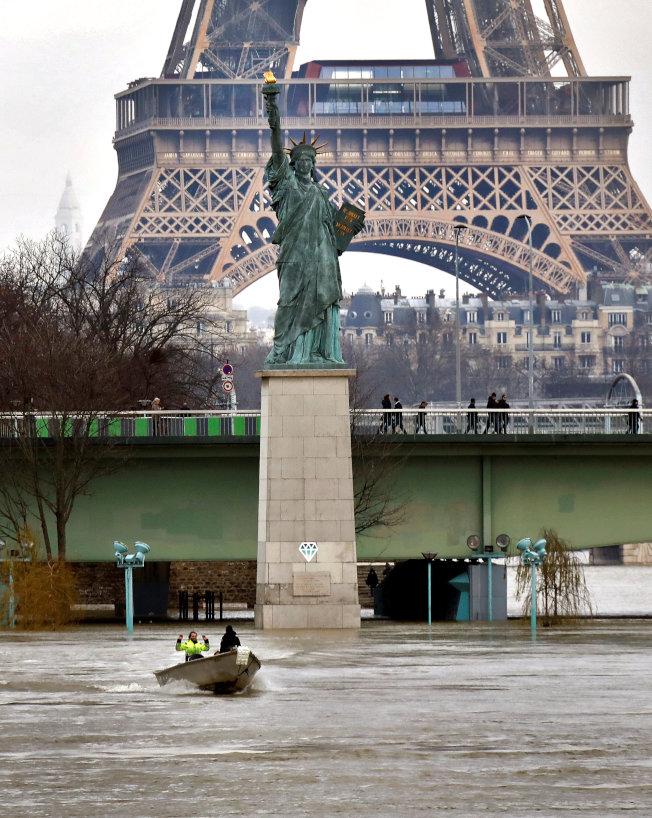 巴黎塞納河中央的人工島天鵝島27日已遭洪水淹沒,僅剩自由女神像還露出河面。(路透)