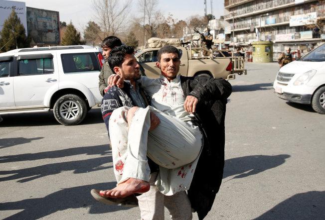 民眾抱起傷者送往醫治。(路透)