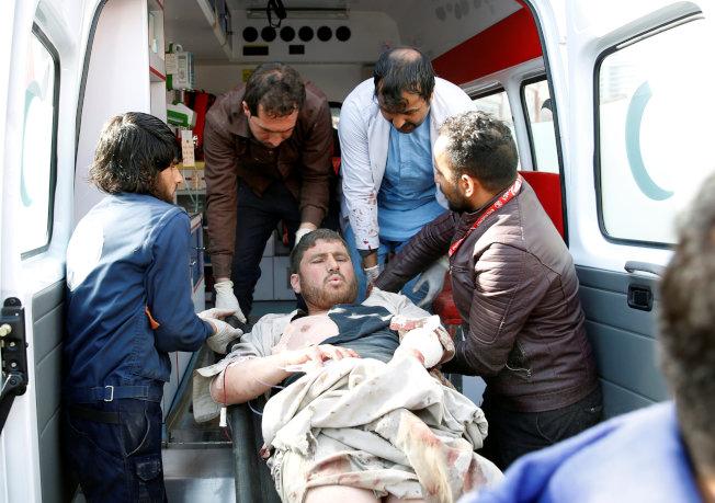 民眾協力把傷者抬上救護車。(路透)