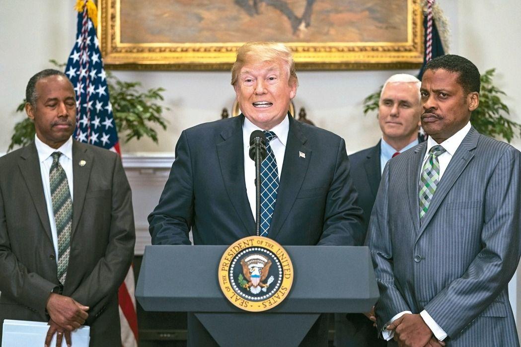 15日為「馬丁路德金恩」紀念日,美國總統川普(中)12日在白宮簽署宣言與發表談話,紀念這位非裔人權運動領袖時,記者高聲問他是否種族歧視,川普未回應。(歐新社)