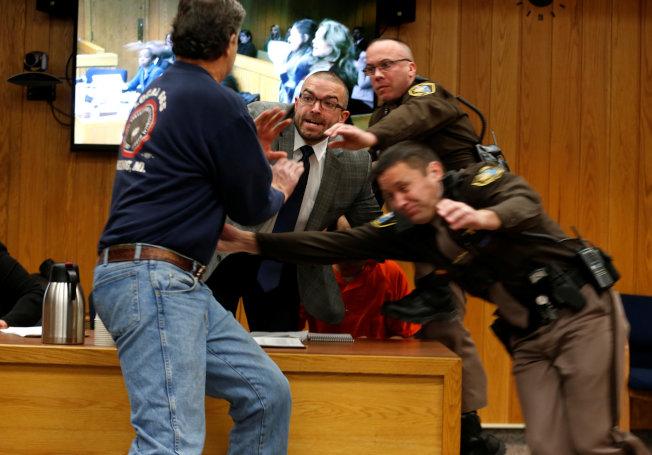 三個女兒均遭體操隊前隊醫納瑟性侵的父親藍道爾.麥格瑞(左)在法庭上衝向納瑟(著紅衣者),但被納瑟的律師及法警擋下,數名法警並將麥格瑞壓制逮捕。(路透)