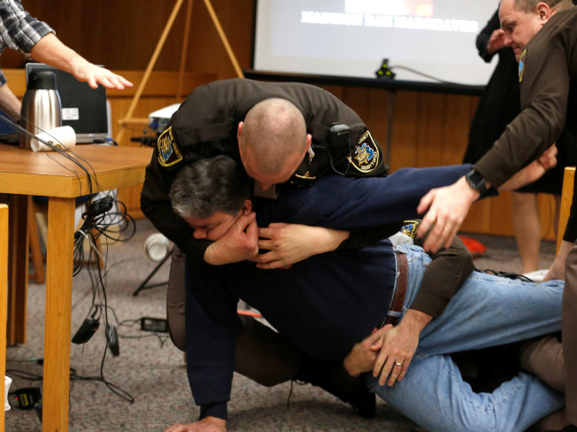 三個女兒均遭體操隊前隊醫納瑟性侵的父親藍道爾.麥格瑞(前)在法庭上衝向納瑟,但被納瑟的律師及法警擋下,數名法警並將麥格瑞壓制逮捕。(路透)