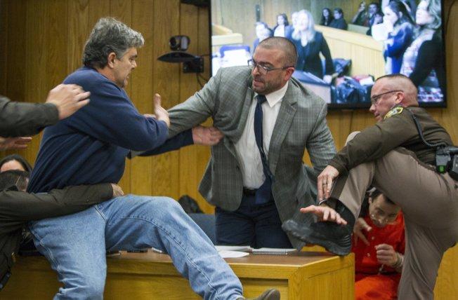三個女兒皆遭體操隊前隊醫納瑟性侵的父親麥格瑞(左)衝向納瑟(右下),但被納瑟的律師擋下來,並遭三名警員制伏。(美聯社)