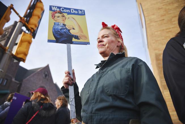在南達科他州舉行的女性大遊行,有人高舉「我們做得到」的圖像。(美聯社)