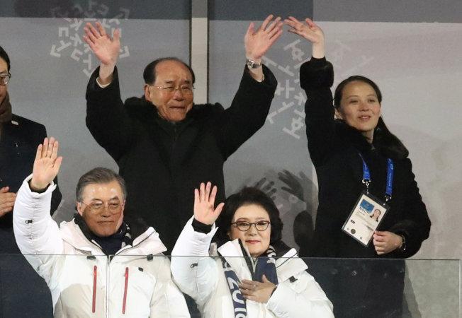 南韓總統文在寅伉儷以東道主身分在平昌冬奧開幕式揮手致意,身後的北韓高官團長金永南及金正恩胞妹金與正感染熱烈氣氛,跟著揮手。(路透)