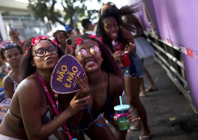 巴西里約熱內盧「Simpatia e Quase Amor」街頭嘉年華遊行,有女性手持扇子上寫著「不即是不」。 (美聯社)