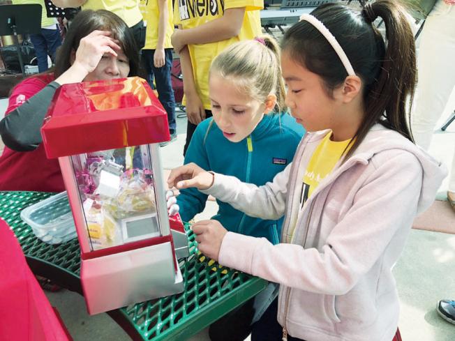 各攤位舉辦的有獎遊戲也很受小朋友歡迎,不論是夾糖果機,還是投球攤位,都可見到排隊等著大展身手的孩子。(記者林亞歆/攝影)