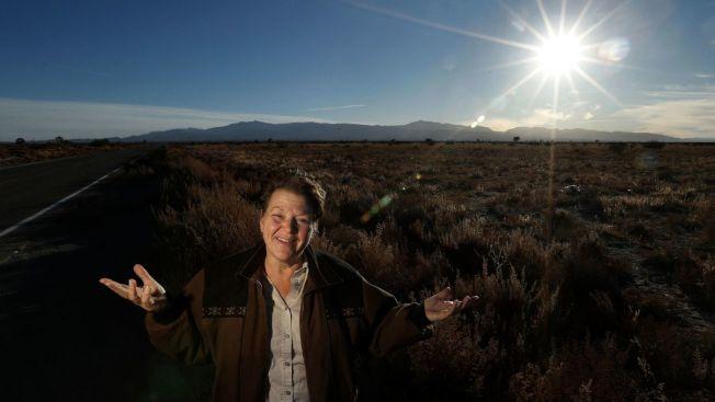 聖伯納汀諾縣小城幻象(El Mirage)市民艾倫(Debi Allen)站在新公路預定地上。(洛杉磯時報)