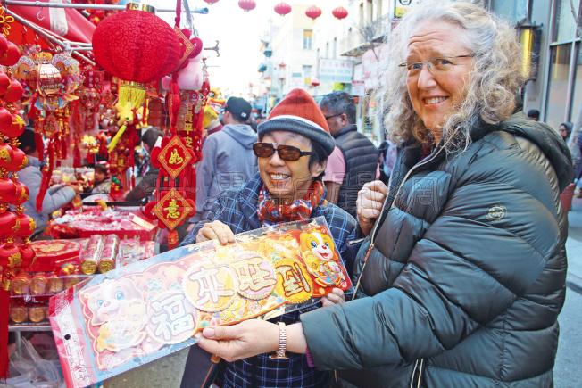 許多非華裔的民眾也在選購年貨,拿著「福來旺到」的對聯。(記者李晗/攝影)
