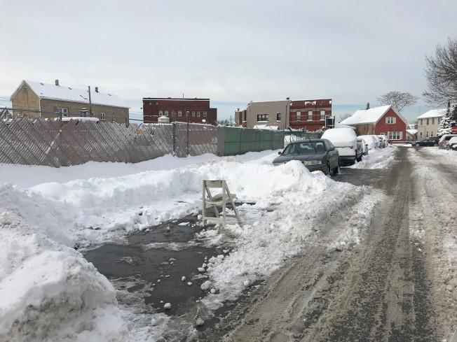 暴雪過後,芝加哥巷弄街道上,時常可以看見清除路邊車位積雪的車主,使用各種物件「佔」住車位。(特派員黃惠玲/攝影)