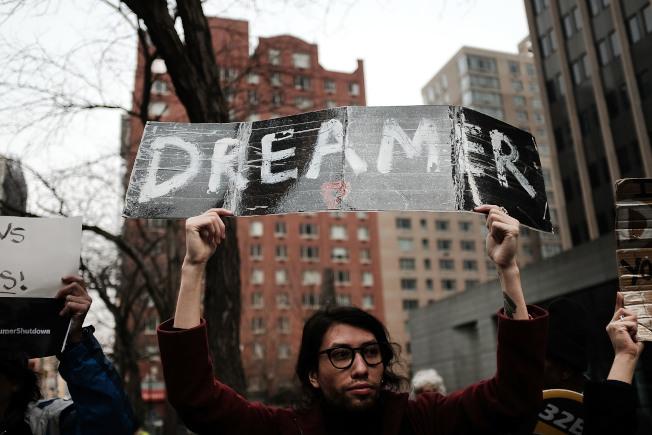 一名紐約支持移民的男子在街頭高舉夢想生的標語牌。(美聯社)