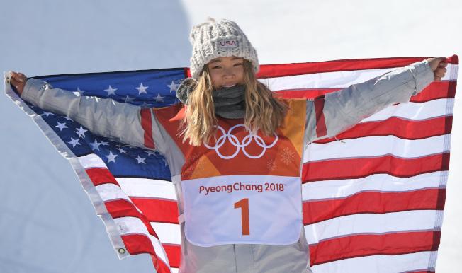 17歲的美國隊韓裔選手金善(Chloe Kim)在女子單板滑雪半管賽項目獲得金牌,披上美國國旗。(Getty Images)