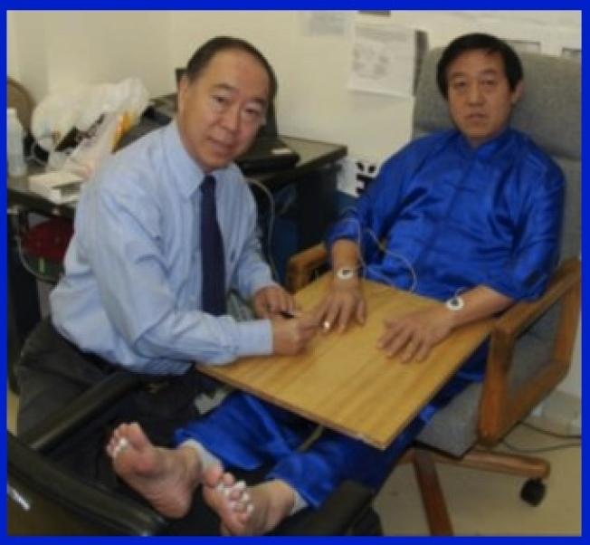 爾灣加大生化教授林欣(左)測試陳正雷的生物電能。(王錤提供)