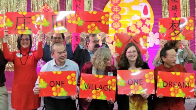 活動組織者邀貴賓高舉「一個村庄,一個夢想」的「踏雪尋梅」尋寶遊戲謎底,高聲號召團結。(記者唐嘉麗/攝影)