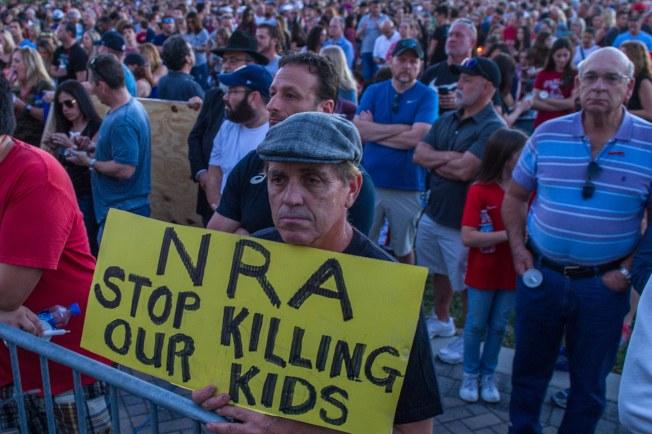 佛羅里達州槍支法律寬鬆,有「槍火之州」之稱。 圖為數以百計佛州帕克蘭市居民15日集會紀念該市一所高中在前一天的槍擊案中死難的17名學生,並舉著標語牌,呼籲「全國步槍協會,停止殺害我們的孩子」。(美聯社)